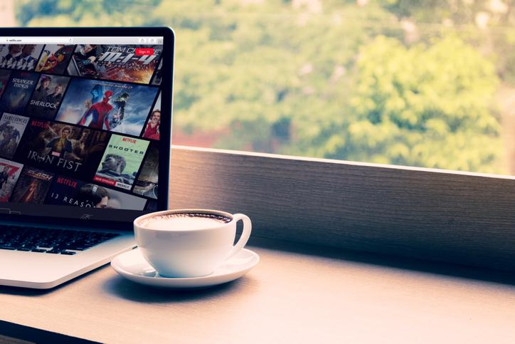 Netflix website showing on screen laptop with macbook pro at cafe. Netflix being popular internationally